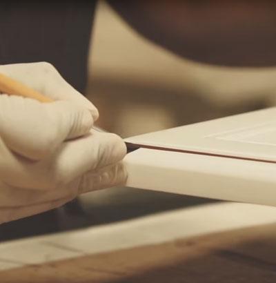 Woodmont Cabinetry artist applies chocolate line glaze to cabinet door