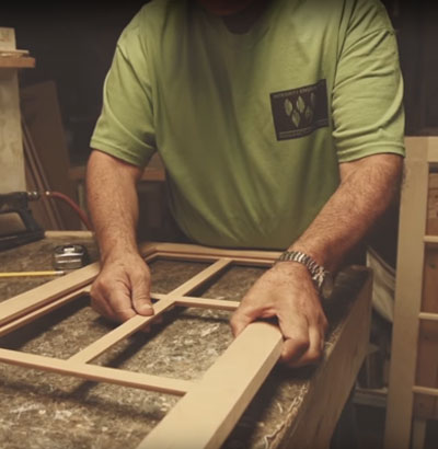Woodmont Cabinetry technician assembles window pane frames to cabinet door